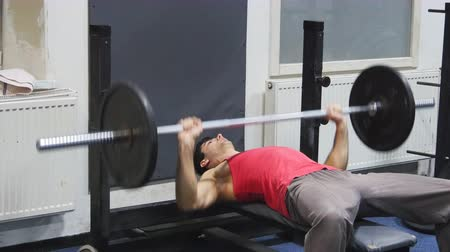 straining : Men lifts up a barbell as a chest exercise