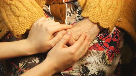 idősek : A young hand comforting a old pair of hands