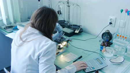 naukowiec : Female doctor scientist lab researcher looking through the microscope. Closeup shot of medical examination process