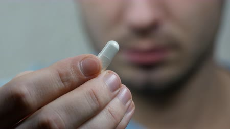 tabletki : Extreme closeup man face taking white pill, mouth view swallowing pills and smile Wideo