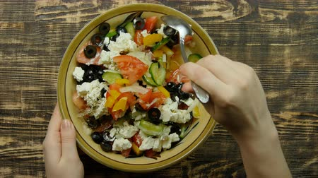 salad : Female hand stirring fresh vegetable salad with cheese feta in the kitchen . The mixing of vegetables. Close-up