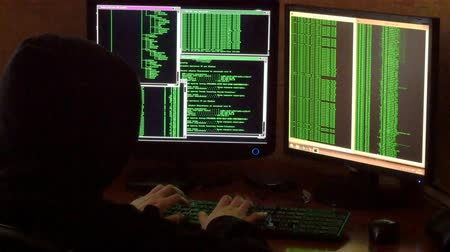 хакер : Hacker breaking code. Criminal hacker with black hood penetrating network system from his dark hacker room.
