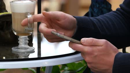покупка товаров : Male hands using smartphone and having cappuccino at cafe in shopping mall. Close-up of man browsing information and scrolling pictures on smart phone