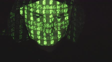 хакер : Face of male hacker in hood working on a computer while green code characters reflect on his face in a dark office room. Source code projected over an angry hostile mans face, black background.