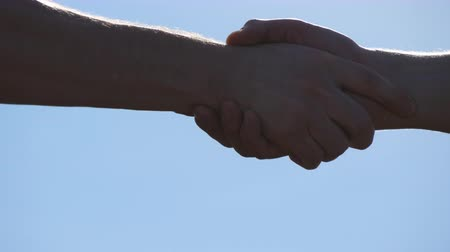 дружба : Friendly handshake of two unrecognizable muscular white men on blue sky background. Shaking of male arms outdoor. Two strong men having firm handshake outside. Teamwork and friendship. Close-up