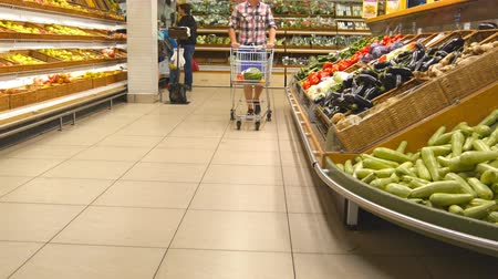 aisles : Young man pushing cart along the grocery aisles in the supermarket. Guy walking with shopping trolley at store