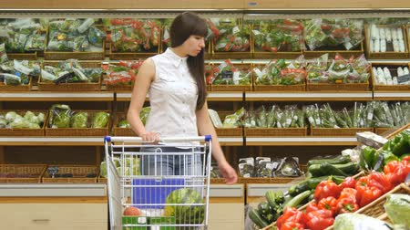 aisles : Young woman pushing cart along the grocery aisles in the supermarket. Girl choosing fresh vegetables in grocery and putting them in the shopping trolley. Girl buying mushrooms at store