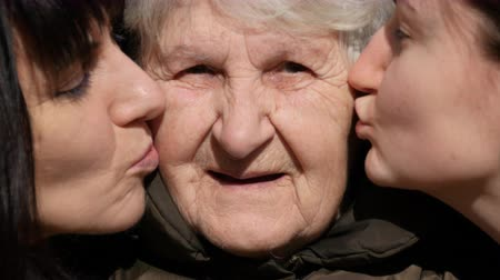 бабушка : Young girl and adult woman kissing grandmother on cheeks, Granny smiling and looking to the camera. Three family generations. Grandmother, mother and granddaughter. Стоковые видеозаписи