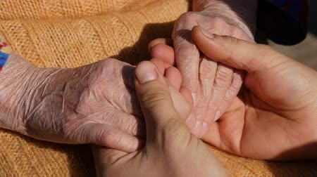 idősek : A young male hands comforting an elderly pair of hands of grandma outdoor close up.