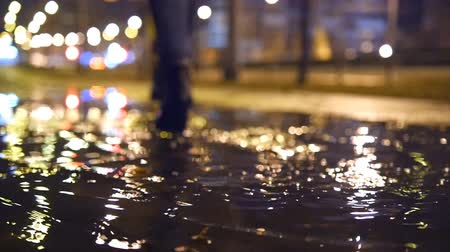 andar : Close up slow motion shot of womans legs stepping into muddy puddle and making splash