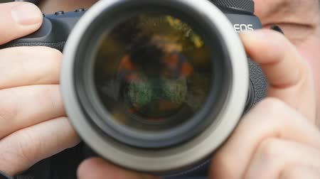 camera operator : Photographer take a picture outdoor. Beautiful reflection of wild tropical nature at the lens of camera. Front view of focusing and shooting with DSLR at sunset. Close up Slow motion Stock Footage