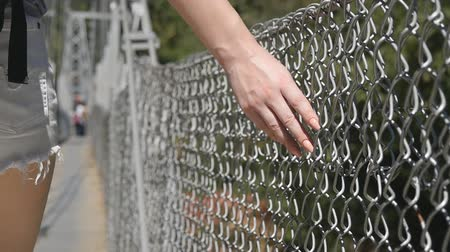 płot : Female hand moving along the surface of grid. Arm of young woman touching metal wire fence. Girl walking during summer vacation and leading his fingers along the guard of bridge. Close up Slow motion