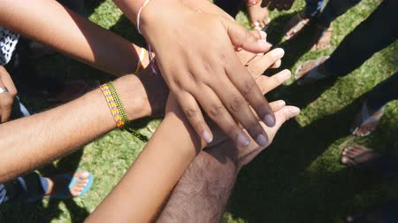 motivasyonel : Arm of all races and colors stacked together one by one in unity and teamwork and then raised. Many multiracial hands getting together in the center of a circle and then cheer. Close up outdoor shot