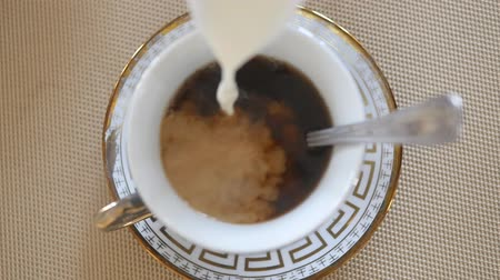 teabag : Milk pouring into tea. Close up Slow motion Stock Footage