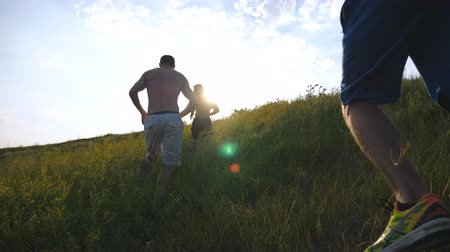 kopec : Group of young men running up the green hill over blue sky with sun flare at background. Male athletes is jogging in nature at sunset. Sport runners going uphill outdoor at sunrise. Slow motion Dostupné videozáznamy