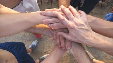segít : Many male hands getting together. Team of athletes putting arms together outdoor. Group of people joining hands together outside. Friends forming arms stack at nature. Teamwork Close up Top view Stock mozgókép