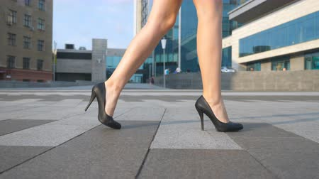 detail : Female legs in high heels shoes walking in the urban street. Feet of young business woman in high-heeled footwear going in the city. Girl stepping to work. Slow motion Close up