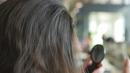 incelik : Young woman looking in the mirror and correcting her hair. Hair care Close up