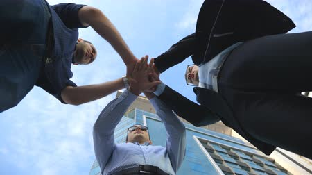 birlik : Three business men standing outdoor near office and stacked arm together in unity and teamwork. Hands of businessman team getting together in the center of a circle and then raised. Low angle of view