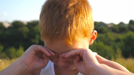 pained : Portrait of sad children with emotions and feelings. Young red hair boy with freckles looking at camera and crying outdoor. Little kid closing eyes with his hands. Close up Slow motion