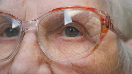 görüş uzaklığı : Old woman looking into the distance and taking off glasses. Granny removes eyeglasses. Close up portrait of grandmother. Slow motion