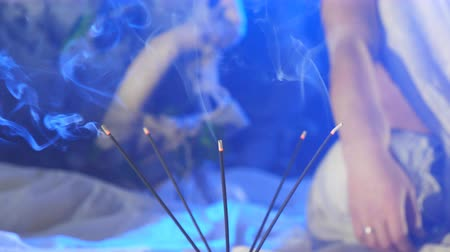 sacramental : Incense smoke from soothing sticks on a blue background. Calm and relax concept. Aromatherapy with cleansing incense smoke. Close up Slow motion