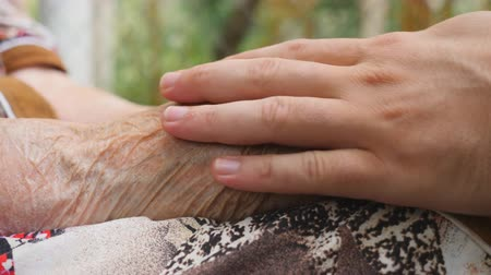 idősek : Young male arms comforting an elderly pair of old woman hands outdoor. Grandson and grandmother spending time together outside. Caring and loving concept. Close up Side view Slow motion
