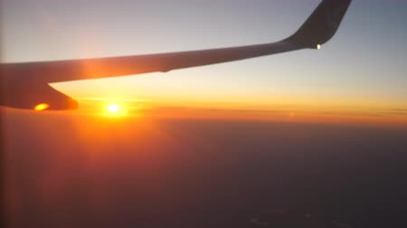 aeroespaço : View from airplane window to beautiful sunrise or sunset. Wing of plane and cloud in sky. Travel concept. Close up