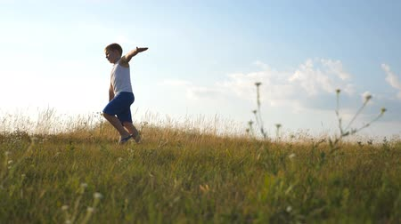 go away : Young boy with raised hands running on green grass at the field on sunny day. Child jogging at the lawn outdoor. Happy smiling male kid having fun in nature on a summer meadow. Slow motion Close up