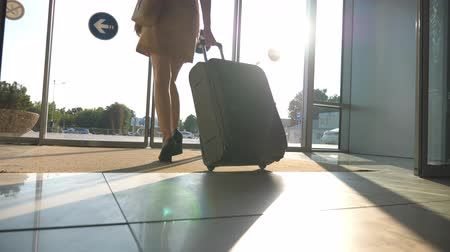 concourse : Business lady going from the airport with her luggage. Woman in heels walking with her suitcase through glass doors from terminal to parking of taxi. Trip or vacation travel concept. Slow motion Stock Footage