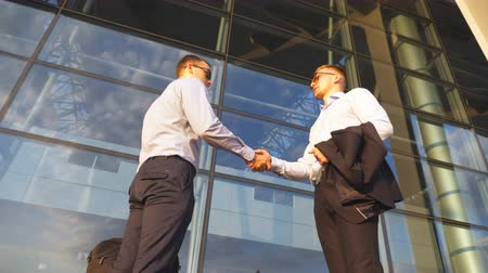 договориться : Two businessmen meeting near office and greeting each other. Colleagues shake hands in the urban environment. Business handshake outdoor. Shaking of male arms outside. Close up Slow motion