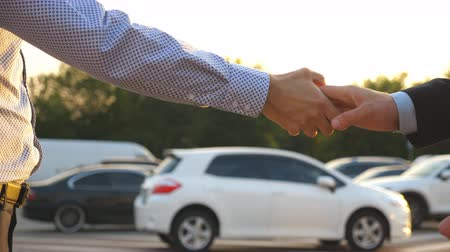 договориться : Male hands in suit giving keys of car to his friend. Arm of businessman passes car key. Handshake between two business men outdoor. Close up Slow motion Стоковые видеозаписи