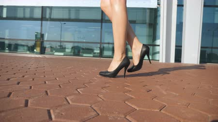 nőiesség : Female legs in high heels shoes walking in the urban street. Feet of young business woman in high-heeled footwear going in the city. Girl stepping to work. Slow motion Close up
