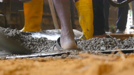 human foot : Close up of unrecognizable indian man shoveling manually wet cement in pile at building site. Local builders working on construction area. Concept of future project. Low angle view