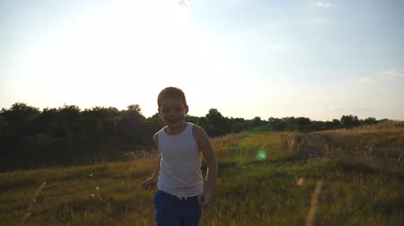 go away : Portrait of happy little boy running at field behind camera. Smiling male kid having fun in nature on a summer meadow. Child jogging at the lawn outdoor on sunny day. Slow motion Stock Footage