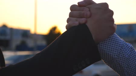 symbol of respect : Two business men having firm friendly handshake outdoor with sun flare at background. Shaking of male arms outside. Friends meet and shake hands in the city background. Close up Slow motion