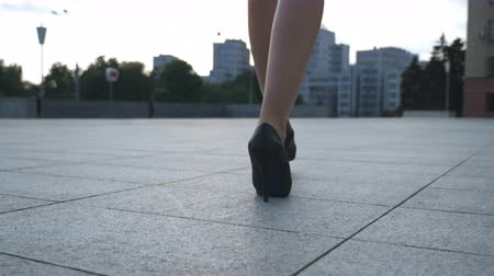 emancipation : Follow to female legs in high heels shoes walking in the urban street. Feet of young business woman in high-heeled footwear going in the city. Girl stepping to work. Slow motion Closeup Rear back view Stock Footage