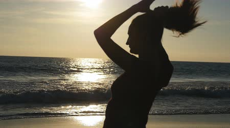 braid hair : Young brunette woman tying ponytail on beach near the sea at sunset. Beautiful girl squeeze her hair at ocean shore at sunrise. Female tourist braiding hair and making hairdo. Haircare Slow motion Stock Footage