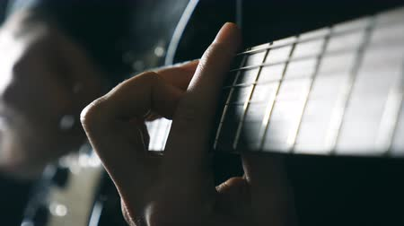 pankáč : Hands of male musician playing at electric guitar. Mens arms plays solo of rock music. Close up fingers of guitarist at the strings. Beautiful black background at studio. Slow motion Close up Dostupné videozáznamy