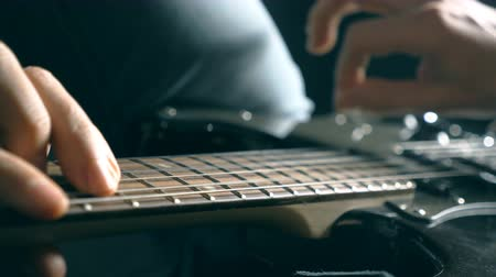 hmatník : Hands of male musician playing at electric guitar. Mens arms plays solo of rock music. Close up fingers of guitarist at the strings. Beautiful black background at studio. Slow motion Close up Dostupné videozáznamy