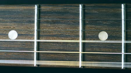 strum : Cord being strummed and seeing it vibrate. Trembling against fret. Close up of guitar string vibrating during playing. Beautiful background with wooden texture. Music performance. Slow motion