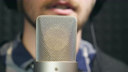голос : Male unrecognizable singer singing song into the microphone at sound studio. Young man recording new melody or song. Working of creative musician. Show business concept. Slow motion Close up