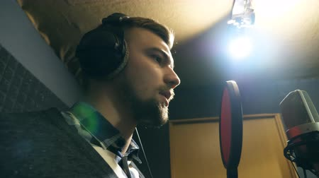 голос : Young man emotionally recording new melody or song. Male singer in headphones singing song into the microphone at sound studio. Working of creative musician. Show business concept. Slow motion Стоковые видеозаписи
