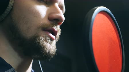 skladatel : Close up of male singer in headphones singing song into the microphone at sound studio. Young man emotionally recording new song. Working of creative musician. Show business concept. Slow motion
