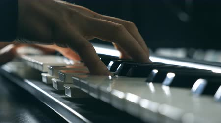 marfim : Close up fingers of pianist at the piano keys. Mens arms plays solo of music or new melody. Hands of male musician playing at synthesizer. Slow motion Top view Isolated shot
