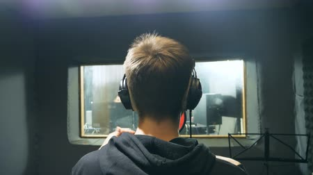compositor : Male singer in headphones singing song at sound studio. Unrecognizable young man emotionally recording song. Working of creative musician. Show business concept. Slow motion Rear back view Vídeos