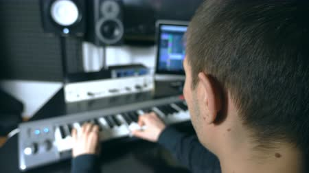 marfim : Male musician playing at synthesizer at sound recording studio. Man plays solo of music. Fingers of pianist at the piano keys. Beautiful background of workplace. Slow motion Rear back view Stock Footage