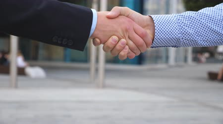 договориться : Colleagues meet and shake hands in the city background. Two businessmen greeting each other in urban environment. Business handshake outdoor. Shaking of male arms outside. Close up Slow motion