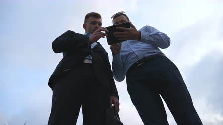 metáfora : Two young businessmen talking and using tablet pc outdoor. Business men working on digital tablet outside with sky at background. Colleagues applying mobile technology. Low angle of view Slow motion