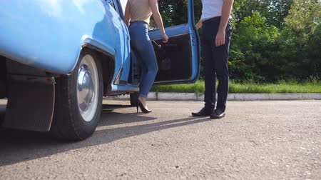 Войти : Man opens and holds the door of old car for the beautiful young woman in high heels shoes. Guy opening door of vintage automobile for female passenger. Girl getting into retro auto. Slow Motion